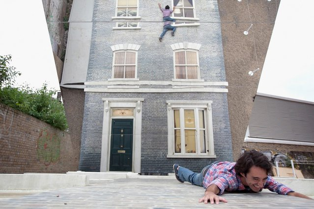 "An man appears in a large-scale installation art piece by Leandro Erlich, named ""Dalston House"", on June 24, 2013 in London, England. Part of the ""Beyond Barbican"" summer series of events, the interactive installation is a full facade of a late nineteenth-century Victorian terraced house built on the ground with a large mirror above it to reflect people as to appear dangling from the structure.  (Photo by Dan Dennison/Getty Images)"
