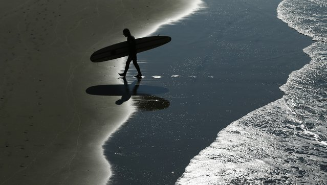 A surfer heads home after riding the morning waves in Oceanside, California January 13, 2015. (Photo by Mike Blake/Reuters)