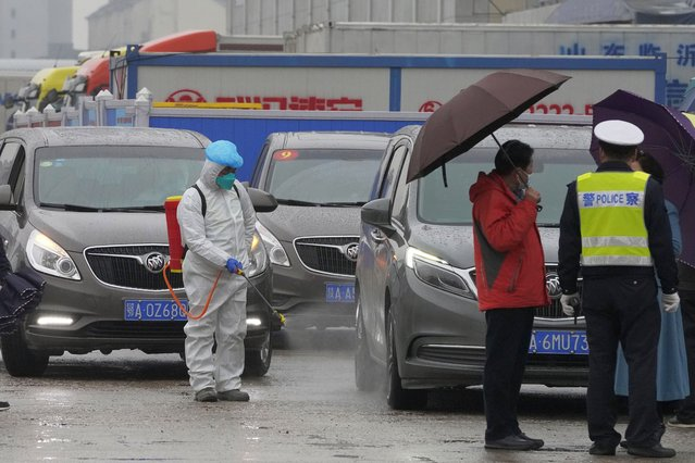 A worker in protective overall disinfects a vehicle from the World Health Organization convoy while they were visiting the Baishazhou wholesale market on the third day of field visit in Wuhan in central China's Hubei province on Sunday, January 31, 2021. (Photo by Ng Han Guan/AP Photo)