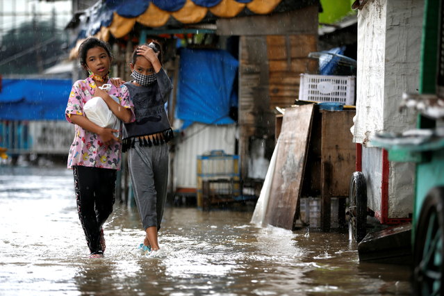 Girls walk along a street affected by floods in  Jakarta, Indonesia, February 8, 2021. (Photo by Willy Kurniawan/Reuters)