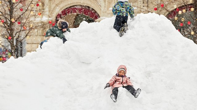 """Children play in a snowdrift during a heavy snowfall at the Red square on February 13, 2021 in Moscow, Russia. A record-breaking snowstorm descended on Moscow on February 12, paralysing traffic, grounding flights and straining efforts of local authorities to respond to the """"snow apocalypse"""". (Photo by Oleg Nikishin/Getty Images)"""