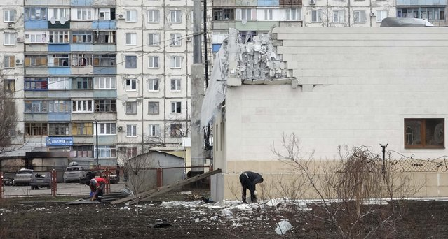 "People remove debris near the building damaged by shelling on Saturday in Mariupol, eastern Ukraine, January 25, 2015. Pro-Russian rebels launched an offensive against the strategic port of Mariupol in eastern Ukraine on Saturday, prompting the European Union's foreign policy chief to warn of a further ""grave deterioration"" in EU-Russian relations. (Photo by Nikolai Ryabchenko/Reuters)"