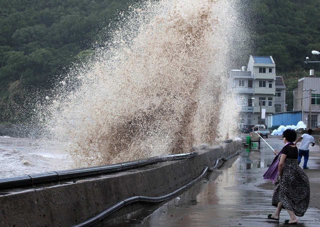 A woman holds a selfie stick to take photos of a wave breaking on the waterfront, as Typhoon Maria approaches, in Taizhou, Zhejiang province, China on July 11, 2018. (Photo by Reuters/China Stringer Network)
