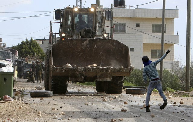 A Palestinian boy throws stones at an Israeli army bulldozer during clashes following a protest against the nearby Jewish settlement of Qadomem, in the West Bank village of Kofr Qadom near Nablus January 30, 2015. (Photo by Abed Omar Qusini/Reuters)