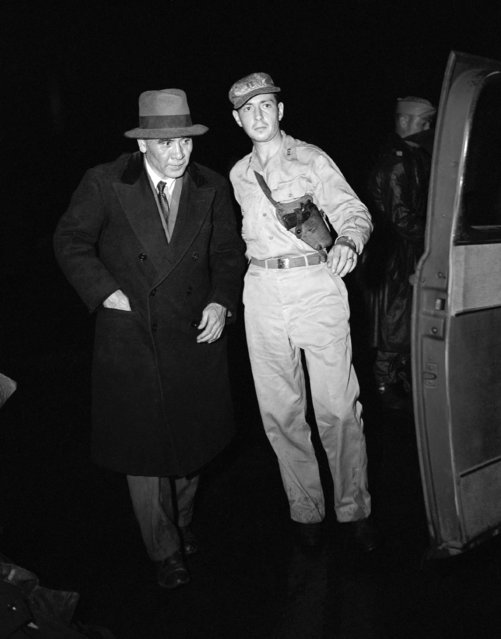 Japanese Lt. Gen. Masaharu Homma, left, is escorted from an Army plane by a military policeman upon arriving in Manila, Philippines on December 13, 1945, for his war crimes trial involving the deaths of 67,000 American and Filipino prisoners of war during the Bataan Death March. (Photo by Max Desfor/AP Photo)