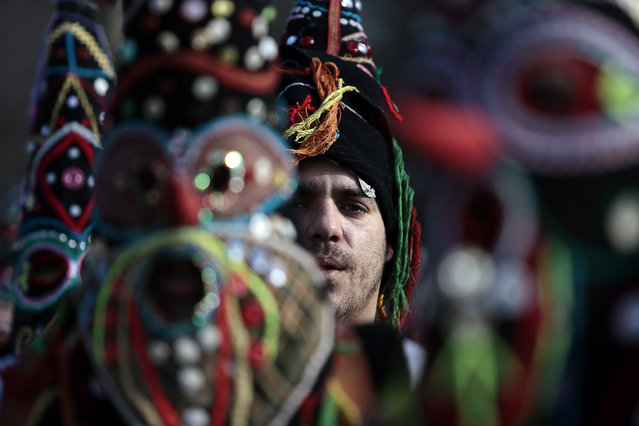 "A Bulgarian dancer is seen between masks as they take part in the second competition day of the 24th International Festival of Masquerade Games  ""Surva"" in the town of Pernik, Bulgaria Saturday, January 31, 2015. (Photo by Valentina Petrova/AP Photo)"