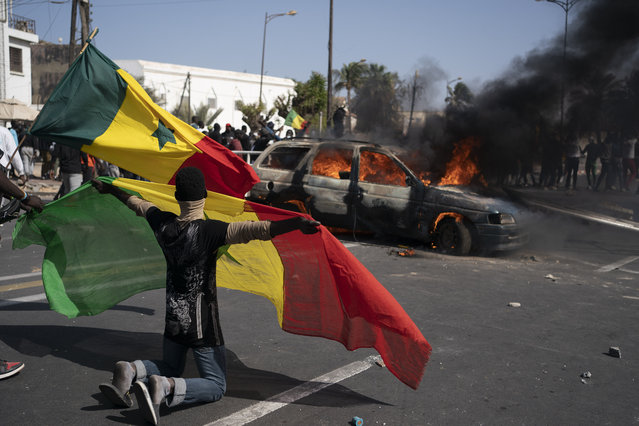 A demonstrator holds a Senegalese flag as he kneels in front of a burning car during protests against the arrest of opposition leader and former presidential candidate Ousmane Sonko, Senegal, Monday, March 8, 2021. (Photo by Leo Correa/AP Photo)