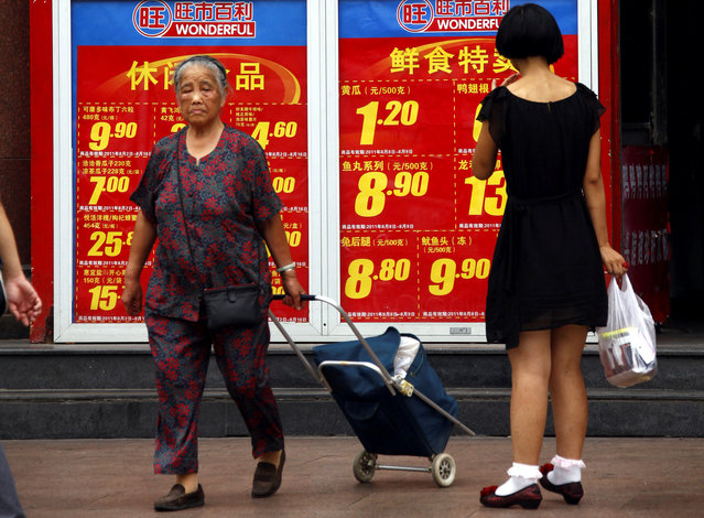 Shoppers walk past and look at a board displaying food prices at a shopping mall in central Beijing August 9, 2011. (Photo by David Gray/Reuters)