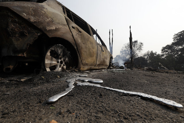 Melted metal is seen under a wildfire- damaged car Tuesday, July 31, 2018, in Lakeport, Calif. Battalion Chief John Messina said Tuesday fire crews slowed the spread of one of the blazes into towns near Clear Lake, including Lakeport, a city of 5,000. He says the fire instead spread into the Mendocino National Forest. (Photo by Marcio Jose Sanchez/AP Photo)