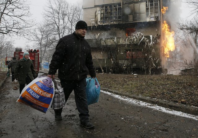 People carry bags containing their belongings past a burning residential block, caused by a recent shelling according to locals, on the outskirts of Donetsk, eastern Ukraine February 9, 2015. (Photo by Maxim Shemetov/Reuters)