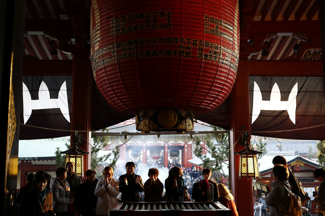 People pray at the Sensoji temple ahead of the New Year holidays in Tokyo, Japan December 30, 2015. (Photo by Thomas Peter/Reuters)