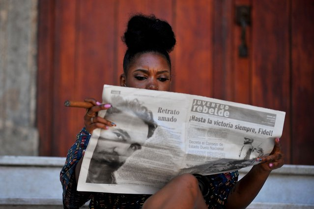 A woman smokes a cigar as she reads the newspaper in a street of Havana, on November 26, 2016, the day after Cuban revolutionary leader Fidel Castro died aged 90. One of the world's longest-serving rulers and modern history's most singular characters, Castro defied 11 US administrations and hundreds of assassination attempts. (Photo by Yamil Lage/AFP Photo)