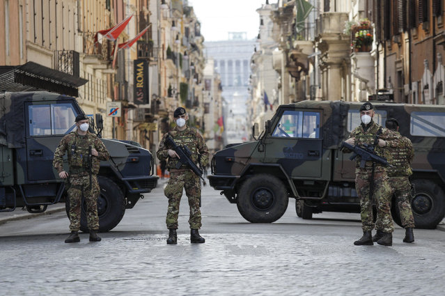 Italian Army officers patrol Rome's central Piazza del Popolo, Saturday, April 3, 2021. Italy went into lockdown on Easter weekend in its effort to battle then Covid-19 pandemic. (Photo by Gregorio Borgia/AP Photo)