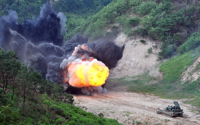 A US Army Assault Breacher Vehicle (ABV) fires the linear demolition charge system during a demonstration at Rodriguez Live Fire Complex in Pocheon, 65 kms northeast of Seoul, on August 14, 2013. A total of six ABVs, a highly mobile and heavily armored minefield and complex obstacle clearing system, were dispatched to South Korea in this year. (Photo by Jung Yeon-Je/AFP Photo)