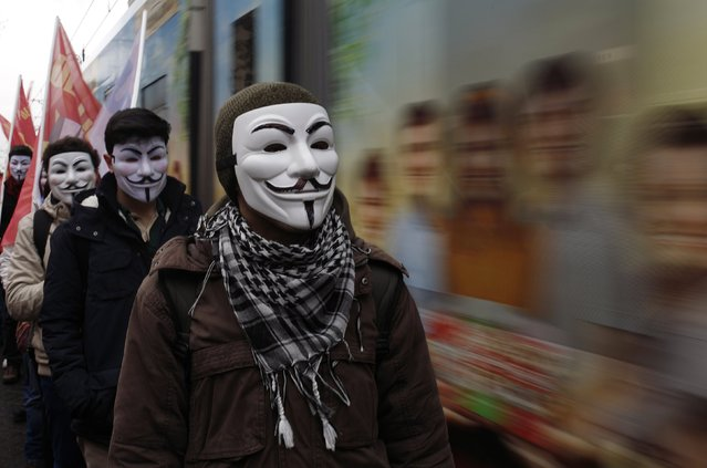 High school students wearing Guy Fawkes masks take part in a protest against the education policies of the ruling AK Party as a tram drives by in Istanbul February 13, 2015. Education is the latest flashpoint between the administration of President Tayyip Erdogan, and secularist Turks who accuse him of overseeing creeping 'Islamisation' in the NATO member state. (Photo by Murad Sezer/Reuters)