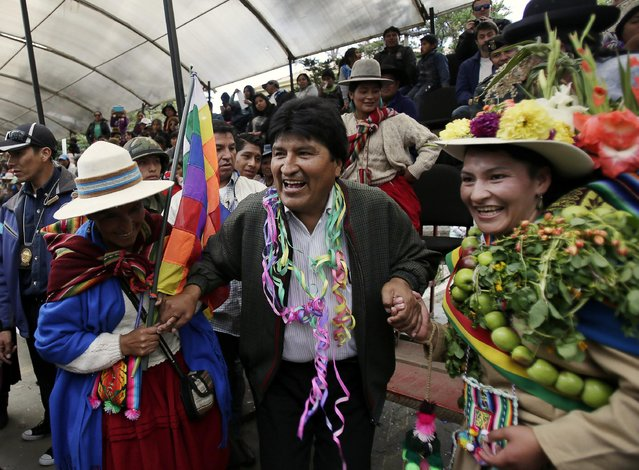 Bolivia's President Evo Morales (C) is invited to dance during the Anata Andina (Andean carnival) parade in Oruro, February 12, 2015. (Photo by David Mercado/Reuters)