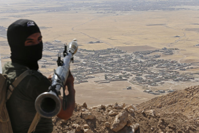 A Kurdish Peshmerga fighter holds a a rocket-propelled grenade launcher as he takes up position in an area overlooking Baretle village (background), which is controlled by the Islamic State, in Khazir, on the edge of Mosul September 8, 2014. (Photo by Ahmed Jadallah/Reuters)