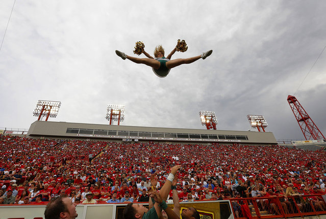 A member of the Edmonton Eskimos cheer squad goes flying through the air during their game against the Calgary Stampeders in the first half of their CFL football game September 2, 2013 in Calgary, Alberta, Canada. (Photo by Todd Korol/AFP Photo)