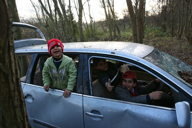 Kurdish children play in an abandoned car in a new migrant camp on January 6, 2016 in Dunkirk, France. Thousands of migrants continue to live in makeshift camps in the port towns of Calais and Dunkirk in northern France, where they try and board vehicles heading for ferries or through the tunnel in an attempt to reach Britain. (Photo by Carl Court/Getty Images)