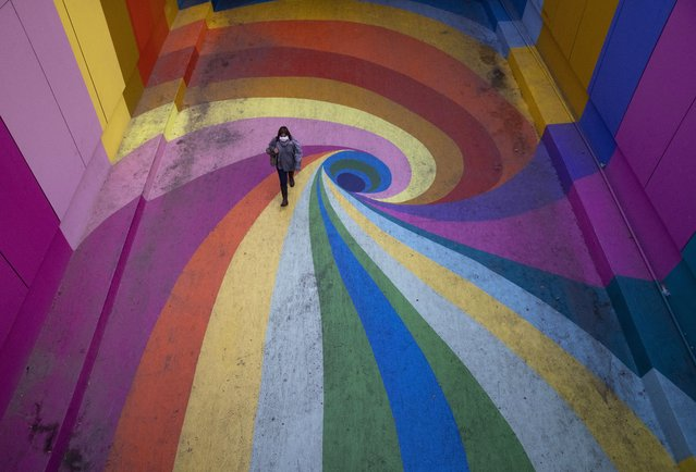 A woman walks through the rainbow-colored Paseo Bandera in Santiago, Chile, Tuesday, April 27, 2021, empty of visitors amid the new coronavirus pandemic. (Photo by Esteban Felix/AP Photo)