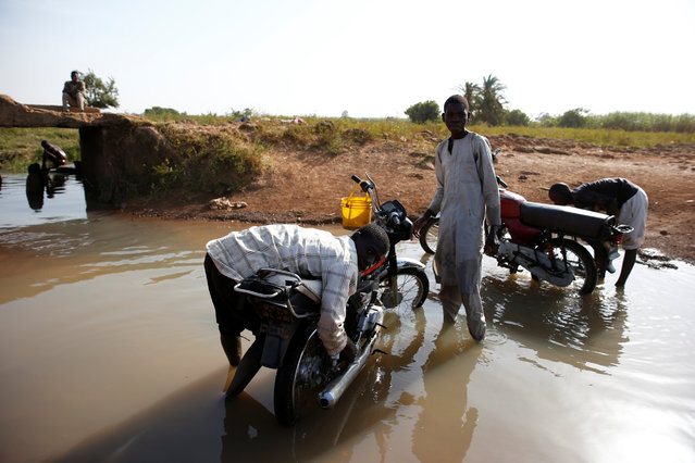 Men wash motorcycles in a water flowing under a bridge on the outskirt of Zaria in Nigeria's northern state of Kaduna November 15, 2016. (Photo by Akintunde Akinleye/Reuters)