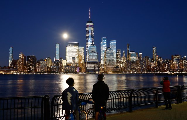 People watch the Super Pink Moon rises above lower Manhattan and One World Trade Center in New York City on April 26, 2021 as seen from Jersey City, New Jersey. (Photo by Gary Hershorn/Getty Images)