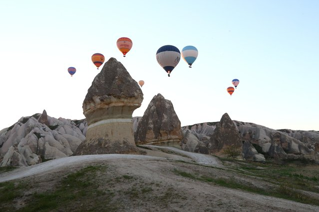 Hot-air balloons glide and take off between the valleys at the historical Cappadocia region, located in Central Anatolia's Nevsehir province, Turkey on April 23, 2021. (Photo by Behcet Alkan/Anadolu Agency via Getty Images)