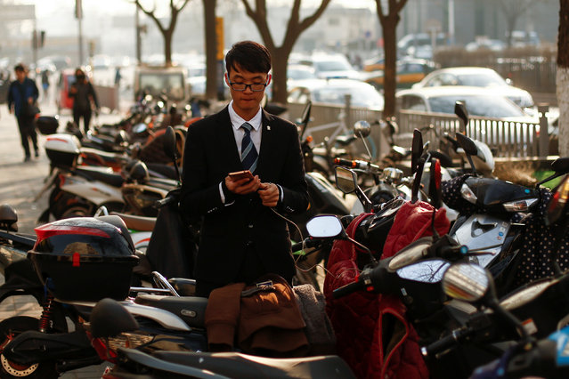 A man in a suit plugs in his mobile phone as he prepares to mount an electric scooter in Beijing, China December 6, 2016. (Photo by Thomas Peter/Reuters)