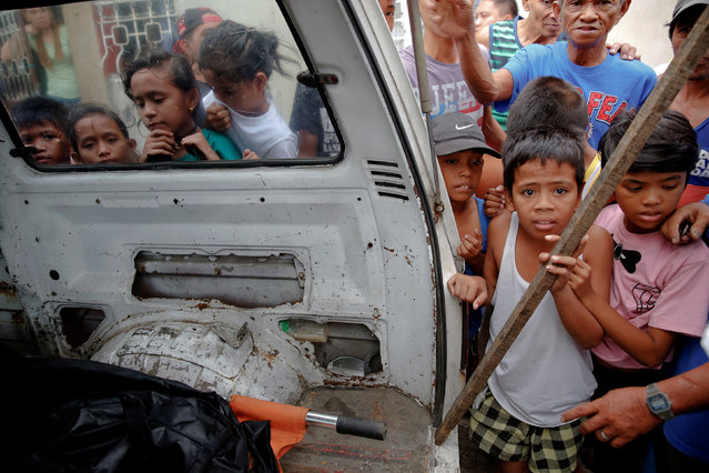 People gather around a funeral parlour vehicle in which the bodies of Noberto Maderal and fellow pedicab driver George Avancena, two men killed during a drug-related police operation, are loaded in Manila, Philippines October 19, 2016. (Photo by Damir Sagolj/Reuters)