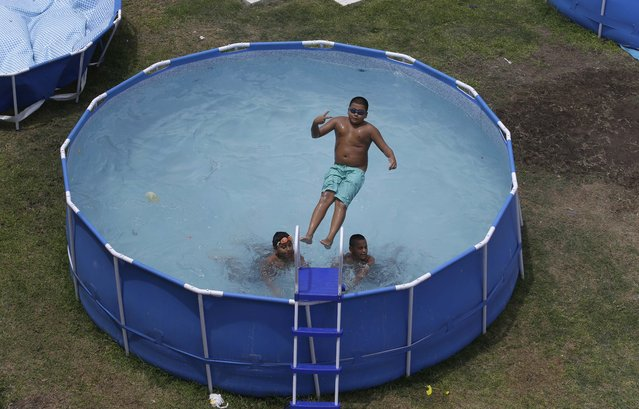 In this Sunday, February 15, 2015 photo, a boy jumps back first into a pool in Callao, Peru. Some parts of Lima have banned swimming pools on the streets, arguing that in February 2014 about 120,000 cubic meters of water was wasted in the arid city, the equivalent of 30 Olympic pools. (Photo by Martin Mejia/AP Photo)