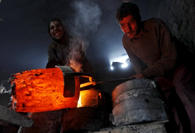 Workers pour melted copper in a mould to make utensils and accessories inside a workshop in Srinagar in this March 27, 2014 file photo. (Photo by Danish Ismail/Reuters)
