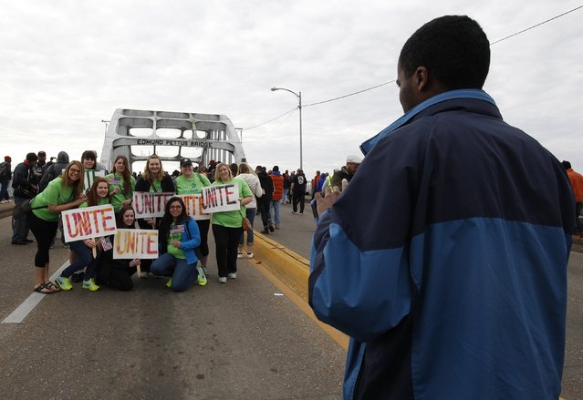 "Students from ""Students Unite"" pose for pictures along the Edmund Pettus Bridge before the beginning of the 50th anniversary of the Selma to Montgomery civil rights march in Selma, Alabama March 8, 2015. REUTERS/Tami Chappell  (UNITED STATES - Tags: POLITICS ANNIVERSARY SOCIETY)"
