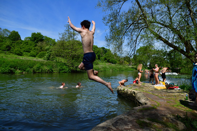 Swimmers dive into the water as they enjoy the hot weather at Warleigh Weir, Bath, United Kingdom on the first day of meteorological summer on Tuesday, June 1, 2021. (Photo by Ben Birchall/PA Images via Getty Images)