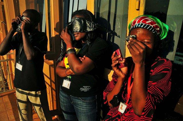 Ugandans watch a hybrid solar eclipse in Kampala. (Photo by Stephen Wandera/Associated Press)