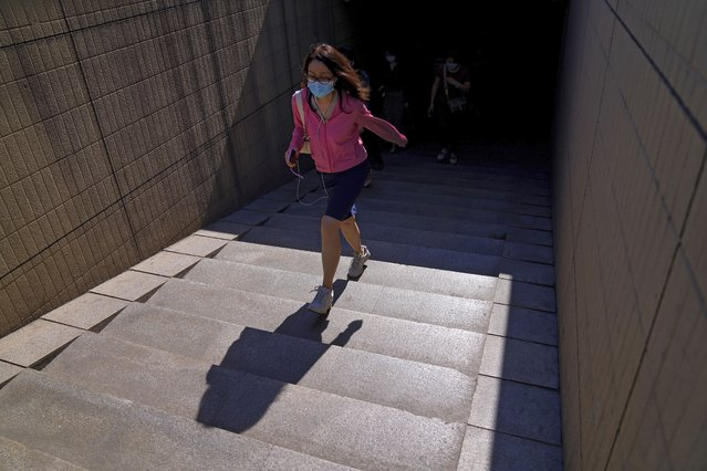 A woman wearing a face mask to help curb the spread of the coronavirus walks out of an underpass tunnel in Beijing, Thursday, June 10, 2021. (Photo by Andy Wong/AP Photo)