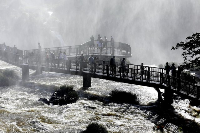 In this March 15, 2015 photo, tourists walk in the spray of Iguazu Falls in Brazil. From walkways and bridges, viewers can count 270 water falls almost 100 meters (330 feet) high. (Photo by Jorge Saenz/AP Photo)