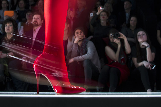 Spectators watch as a model displays a creation by Russian designer Slava Zaitsev during Fashion Week, in Moscow, Russia, Friday, March 27, 2015. (Photo by Pavel Golovkin/AP Photo)