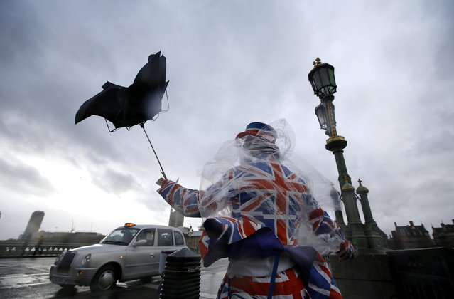 A man giving out leaflets to tourists is blown by the wind in Westminster in London, Monday, February 8, 2016. Winds of nearly 100mph battered Britain after another storm slammed into the south coast bringing fierce gusts and torrential downpours. (Photo by Kirsty Wigglesworth/AP Photo)