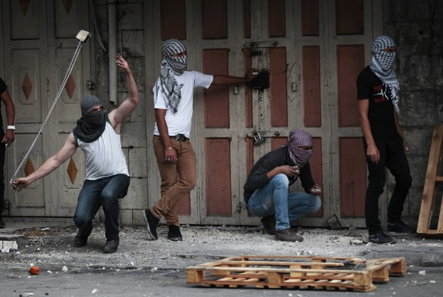A Palestinian protester uses a sling to throw a stone during clashes with Israeli security officers following the funerals of three Palestinians, in West Bank city of Hebron November 27, 2013. Israeli security officials said their forces killed three Palestinian militants on Tuesday who were part of an al Qaeda-linked network in the West Bank. (Photo by Ammar Awad/Reuters)