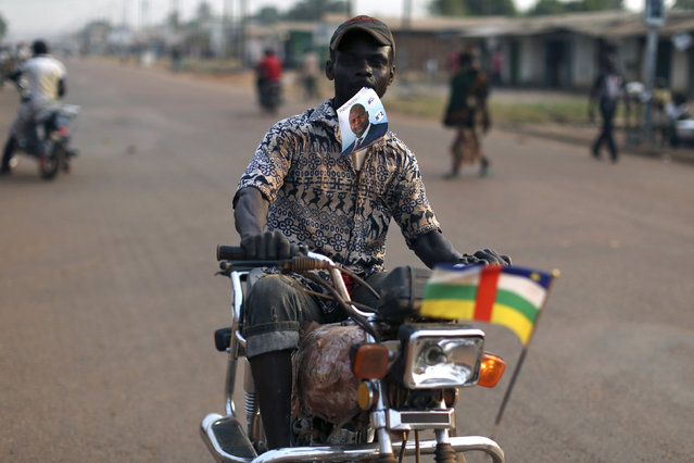 A motorcyclist holds in his mouth a picture of Faustin-Archange Touadera, who will be ruining against  Anicet-Georges Dologuele in the second round of presidential election next Sunday, in the mostly muslim PK5 neighbourhood of the capital Bangui, Central African Republic, February 9, 2016. (Photo by Siegfried Modola/Reuters)