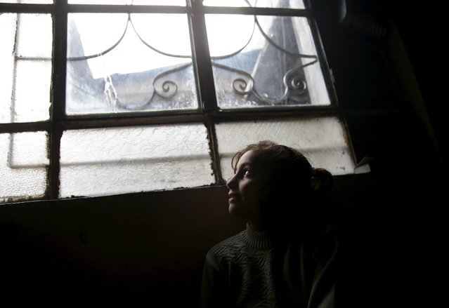 Hadeel, 10, the daughter of Shahrour, looks out of a window at home in the besieged town of Arbeen, in Damascus suburbs, Syria February 6, 2016. (Photo by Bassam Khabieh/Reuters)