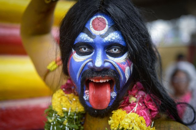 Artists dressed as Hindu gods reacts to the camera during the Bonalu festival procession in Secunderabad, the twin city of Hyderabad, on July 26, 2021. (Photo by Noah Seelam/AFP Photo)