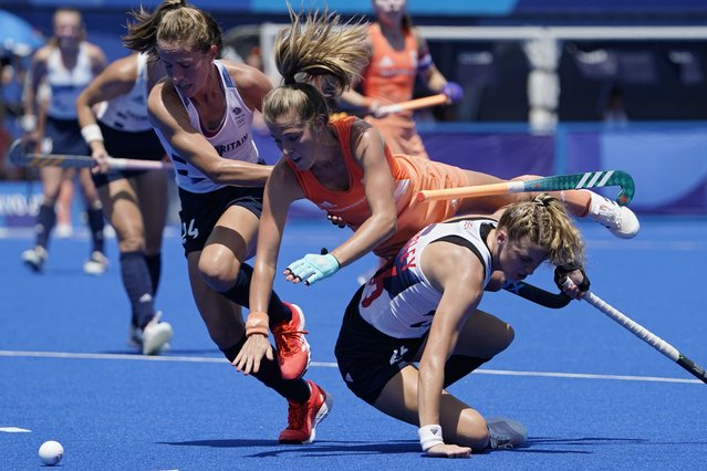 Netherlands' Xan Gerdien de Waard (7) falls over Britain's Lily Owsley (26) during a women's field hockey semi-final match at the 2020 Summer Olympics, Wednesday, August 4, 2021, in Tokyo, Japan. (Photo by John Minchillo/AP Photo)