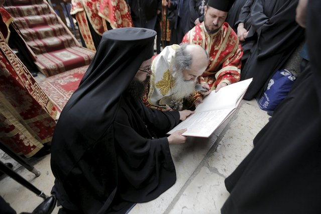 Greek Orthodox Patriarch of Jerusalem Metropolitan Theophilos (C) reads from a book during the washing of the feet ceremony outside the Church of the Holy Sepulchre in Jerusalem's Old City, April 9, 2015, ahead of Orthodox Easter. (Photo by Ammar Awad/Reuters)