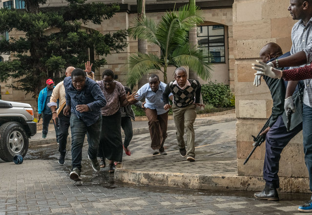 People run for cover after being rescued from the Dusit Hotel on January 15, 2018 in Nairobi, Kenya. A current security operation is underway after terrorists attacked the hotel. (Photo by Andrew Renneisen/Getty Images)