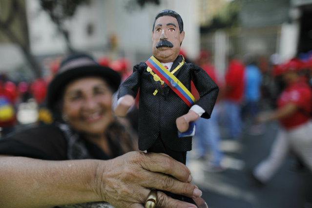In this January 10, 2019 photo, a supporter of Venezuela's President Nicolas Maduro holds a ceramic doll in his likeness outside the Supreme Court where he is being sworn-in for a second term in Caracas, Venezuela. Maduro was sworn in for a six-year term amid international calls for him to step down and a devastating economic crisis. (Photo by Ariana Cubillos/AP Photo)