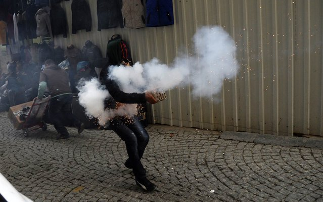 A Kurdish student protestor fires fireworks against Turkish riot policemen on December 24, 2013, in downtown Istanbul, during an anti-government protest marking the second anniversary of a Turkish military air strike aimed at Kurdish rebels that killed 34 civilians working as smugglers at the Turkey-Iraq border in Sirnak. (Photo by Bulent Kilic/AFP Photo)