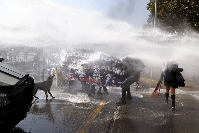 Protesters are hit by a jet of water as they clash with riot police during a demonstration against the government to demand changes in the education system at Santiago, April 16, 2015. (Photo by Ivan Alvarado/Reuters)