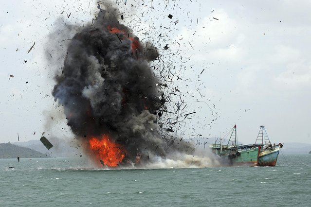 Debris fly into the air as foreign fishing boats are blown up by Indonesian Navy off Batam Island, Indonesia, Monday, February 22, 2016. Authorities on Monday sank dozens of fishing boats caught operating illegally in Indonesian waters as part of the country's campaign to battle illegal fishing. (Photo by M. Urip/AP Photo)