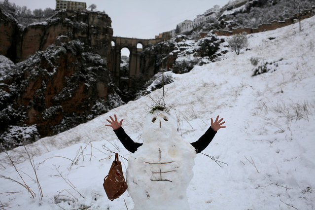 """A man plays with a snowman in front of the """"Puente Nuevo"""" (New Bridge) during a snowfall in Ronda, near Malaga, Spain January 19, 2017. (Photo by Jon Nazca/Reuters)"""